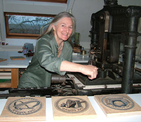 Edwina Ellis in her studio with Pound Coin linocuts & Albion press